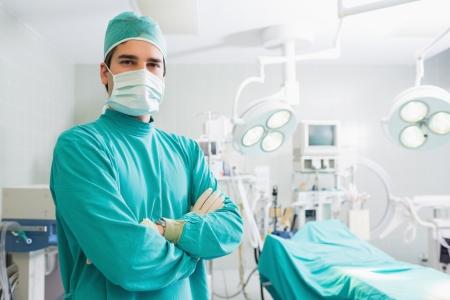 cirujano: Grave cirujano de pie con los brazos cruzados en un quir�fano Foto de archivo
