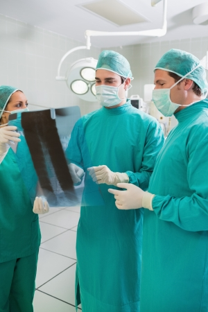 Close up of a surgical team examining a X-ray in an operating theatre photo