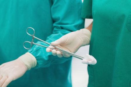 Close up of a surgical scissors with a compress in an operating theatre photo