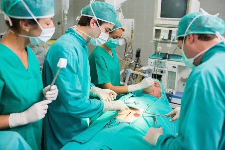 Concentrated surgeons in an operating theatre Stock Photo - 16229089