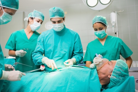 Surgical team performing on a patient belly in an operating theatre photo