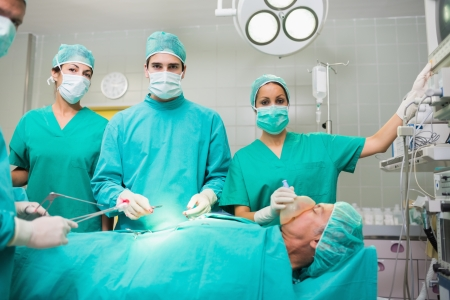 Surgical team looking at camera in an operating theatre photo