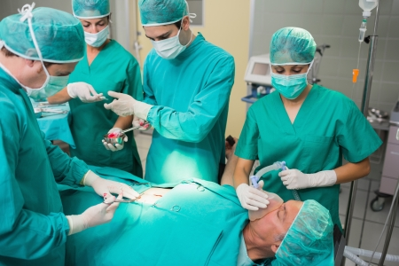 Nurse giving a surgical tool to a surgeon in an operating theatre photo