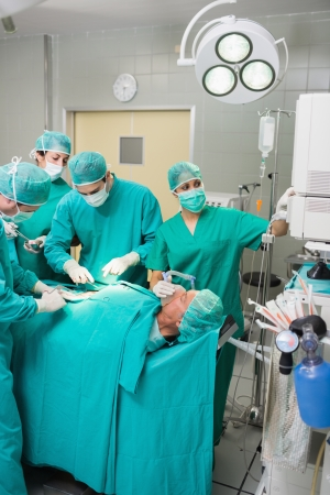 Nurse adjusting a monitor in an operating theatre photo