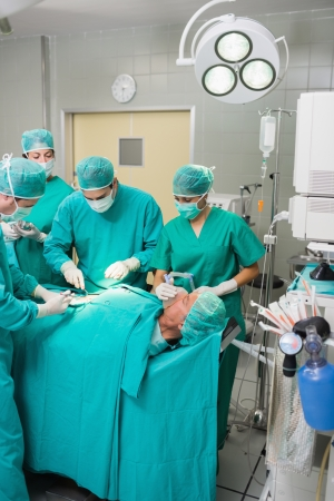 Surgeons and nurses around a patient in an operating theatre Stock Photo - 16229039