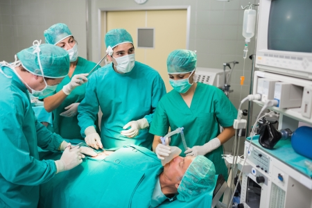 Nurse drying forehead of a surgeon next to a patient in an operating theatre photo