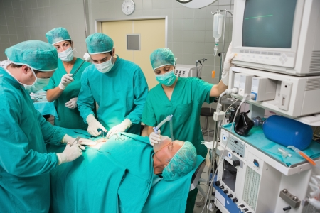 Surgical team operating a patient belly in an operating theatre photo