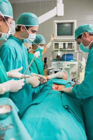 Side view of a surgical team next to a patient in an operating theatre photo