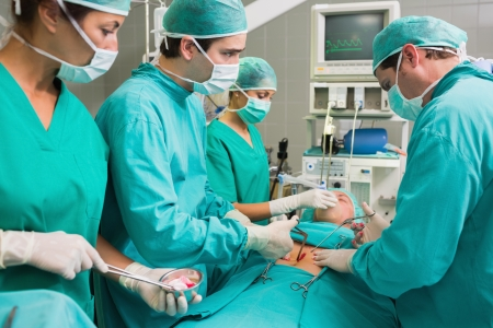 Surgeon operating with surgical tools in an operating theatre Stock Photo - 16229316