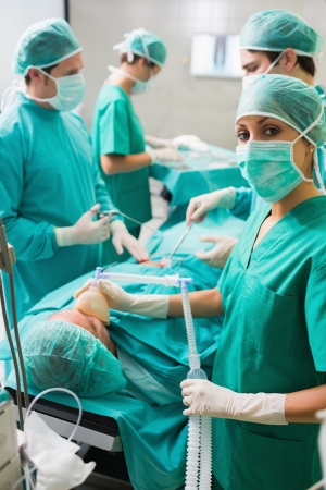 Nurse looking at camera while holding an oxygen mask in an operating theatre photo