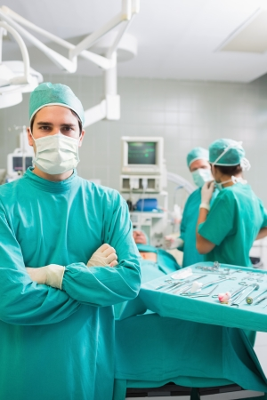 Surgeon looking at camera with arms crossed in an operating theatre Stock Photo - 16229033