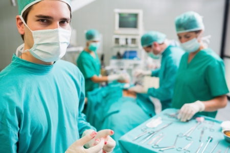 surgery tools: Surgeon wearing bloody gloves while looking at camera in an operating theatre