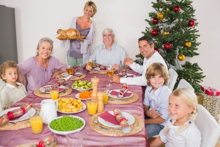 Mother bringing turkey to dinner table at christmas photo