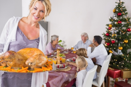 Proud mother showing roast turkey at christmas photo