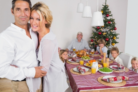 Husband and wife embracing beside the dinner table at christmas photo