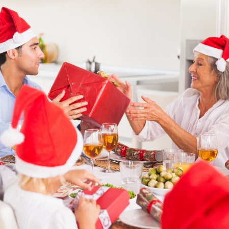 Family exchanging christmas presents around the dinner table wearing santa hats Stock Photo - 16228409