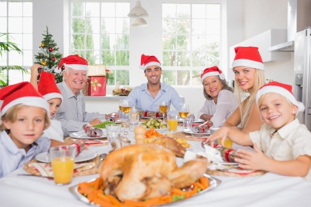 Smiling family around the dinner table at christmas wearing santa hats photo