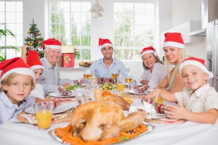 Sourire de la famille autour de la table à Noël wearing santa chapeaux