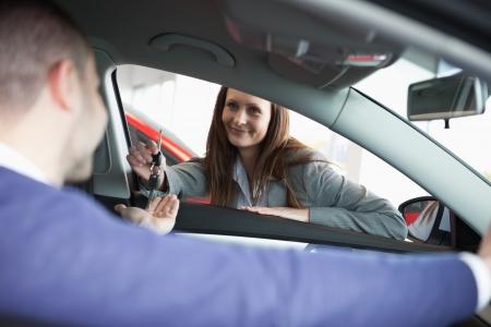 Woman giving car keys to a customer Stock Photo - 18095202