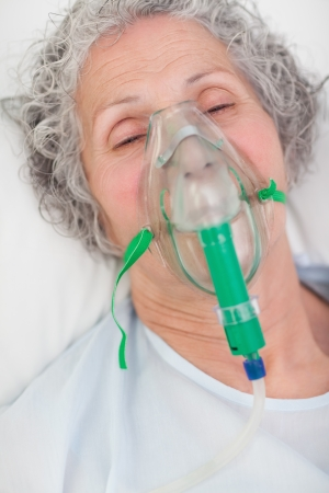 oxigen: Elderly closing her eyes while lying in a hospital bed with an oxigen mask