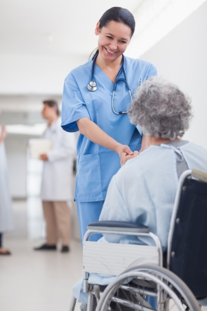 Doctor greeting recovering senior patient in wheelchair in a hospital corridor Stock Photo - 18095362