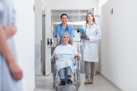 Smiling nurse assisting senior woman sitting in a wheelchair in a hospital corridor photo