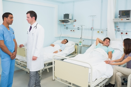 Doctor and male nurse in a hospital room with patient resting