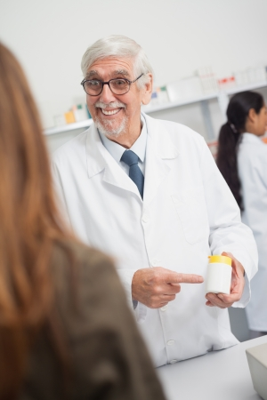 doctor giving glass: Smiling male pharmacist pointing at drugs in a hospital