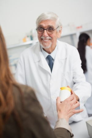 Smiling male pharmacist pointing at a box of pills in a hospital photo