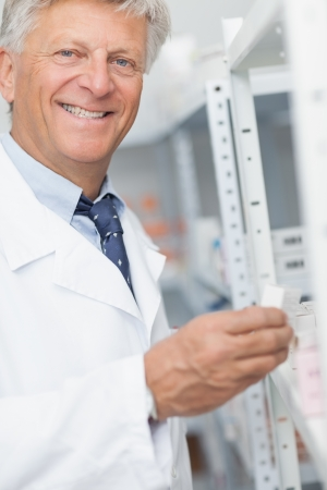 Smiling pharmacist looking at pills in a shelf in a hospital photo