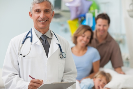 paediatrics: Doctor standing in a hospital room with a family Stock Photo