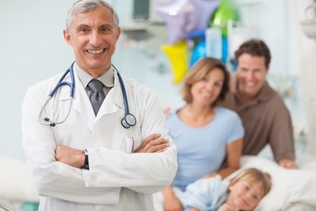 Family doctor: Doctor standing in a hospital room while crossing his arms with a family Stock Photo