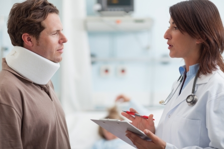 neck brace: Doctor talking to male patient with a collar on in a hospital Stock Photo