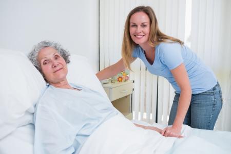 recovery bed: Donna che tiene la mano di un paziente in una stanza d'ospedale Archivio Fotografico