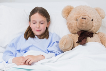 sick teddy bear: Child sleeping with a teddy bear while lying in a hospital bed Stock Photo
