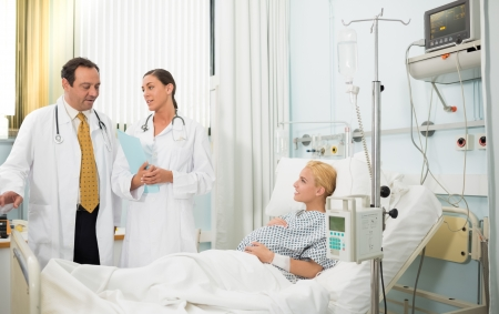 Pregnant patient in her bed talking with doctors at hospital photo