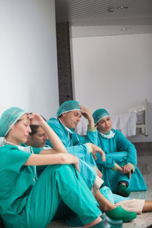 Team of exhausted surgeons sitting on the floor in a hospital photo