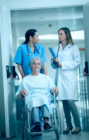 Nurse wheeling a senior patient patient in a hallway in a hospital photo