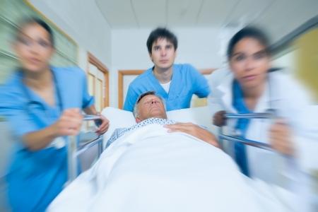 emergencia: Equipo m�dico de correr en un pasillo de hospital con un paciente en una cama