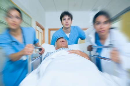 Team of doctor running in a hospital hallway with a patient in a bed photo