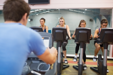 instructs: Man instructs spinning class to four women at gym Stock Photo