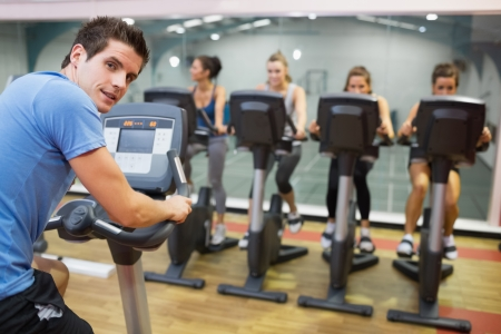 Male instructor at spinning class with four women in gym photo