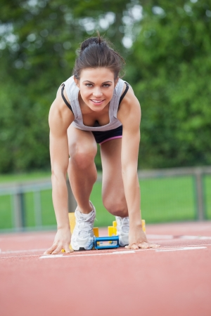 Female athlete at athletic starting blocks on track field Stock Photo - 18095230