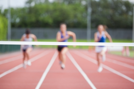 caucasian race: Female athletes running towards finish line on track field