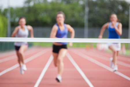 jogging track: Female athletes racing towards finish line at track field Stock Photo