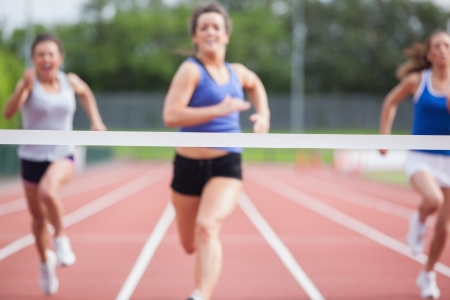 Female athletes close to finish line at track field Stock Photo - 18095089