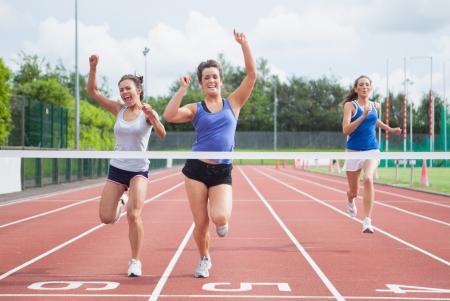 tied hair: Atlete festeggiare mentre attraversano traguardo sul campo di pista