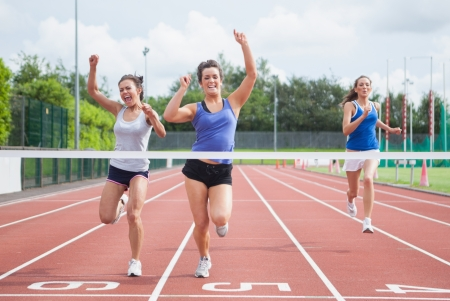 winning woman: Female athletes celebrating as they cross finish line on track field Stock Photo