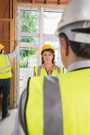 Woman looking upset at architect while man is measuring in house site photo