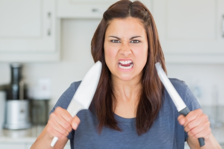 threateningly: Angry woman holding up knives threateningly
